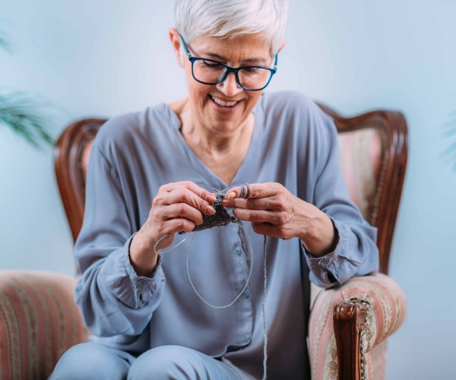 Knitting. Senior woman knitting at home. Cognitive enhancement ability.